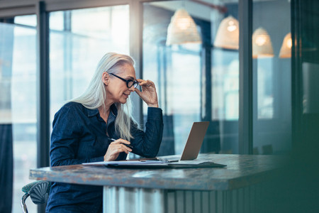 Senior business woman working on laptop in office