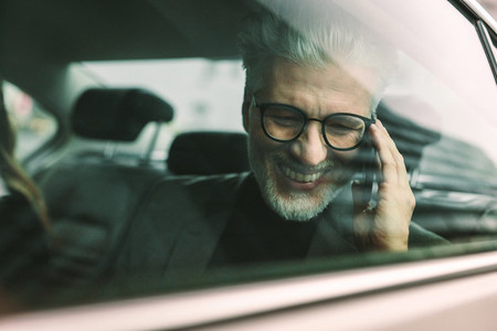 Smiling senior businessman making phone call in cab