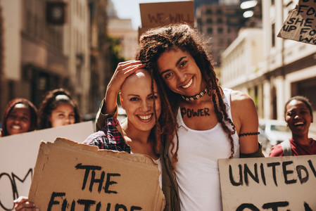 Happy women with placards protesting outdoors