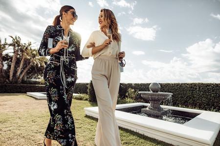 Stylish women friends with wine walking outdoors