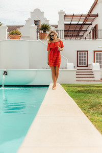 Woman walking by the pool of luxurious home