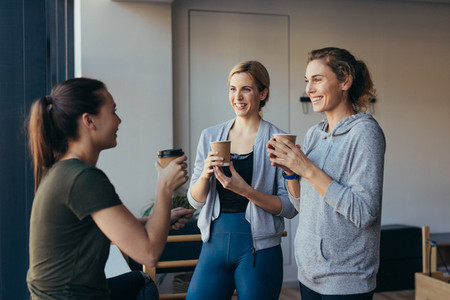 Fitness women drinking coffee after workout in a gym