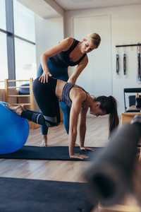 Pilates woman training with an exercise ball at gym