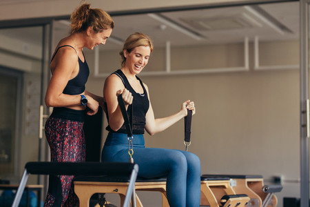 Smiling women doing pilates workout at the gym