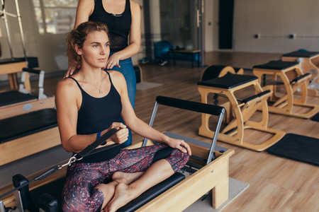 Woman pulling a stretch band  sitting on pilates training machin