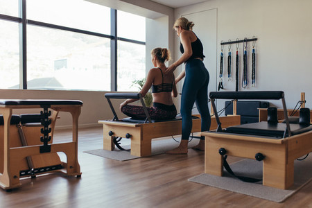 Trainer guiding a pilates woman for correct posture at the gym