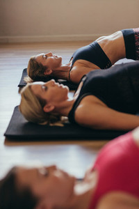 Women doing pilates workout at the gym lying on the floor