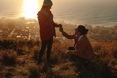 Man proposing woman with wild flower on mountain