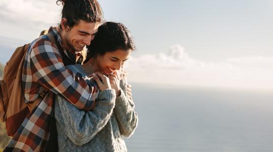 Man embracing woman outdoors
