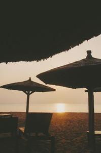 Tropical beach umbrella sunset