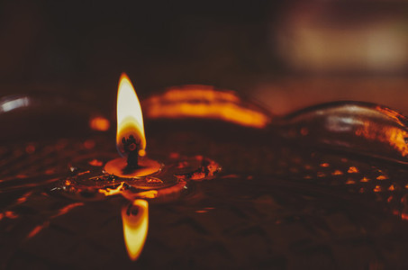 Burning Candle Floating In Oil