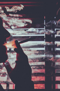 Silhouetted person smoking joint
