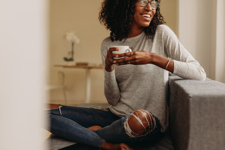 Woman enjoying a cup of coffee sitting at home