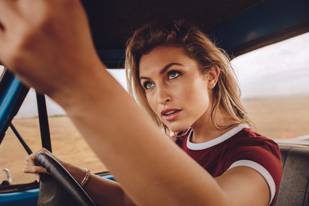 Woman driving car and setting rear view mirror