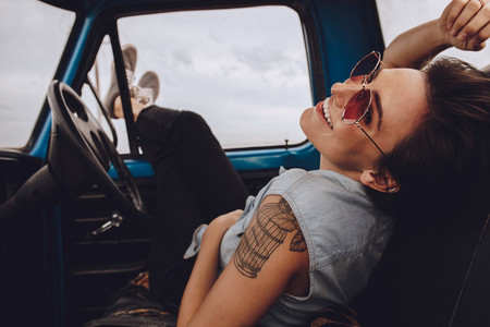 Woman on road trip relaxing in car