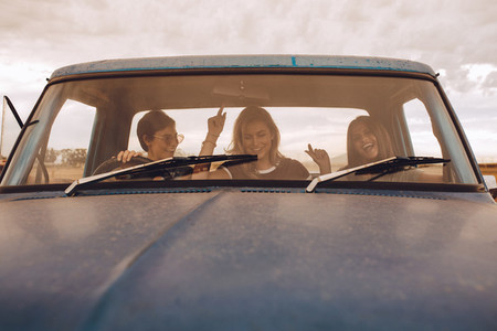Group of females having fun traveling in a truck