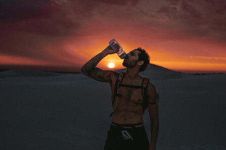 Athlete drinking water during workout in desert
