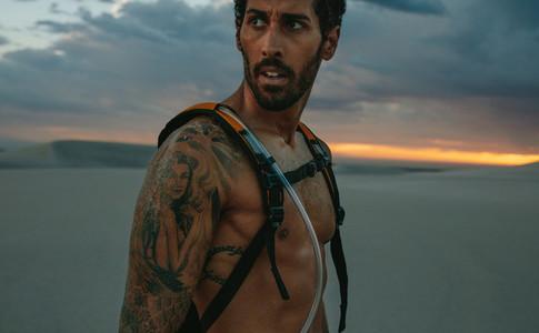 Man taking break from workout in desert