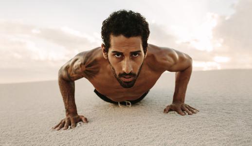 Male athlete doing push ups on desert sand
