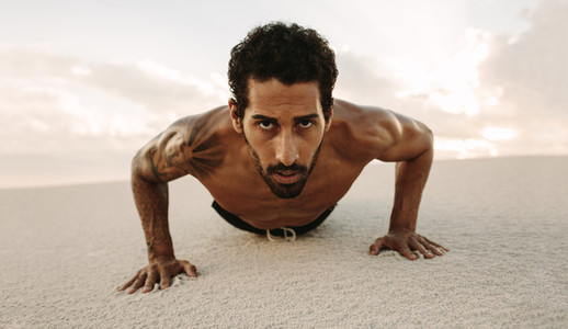 Male athlete doing push ups on desert sand
