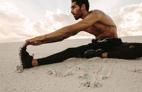 Athlete doing stretching on sand dune