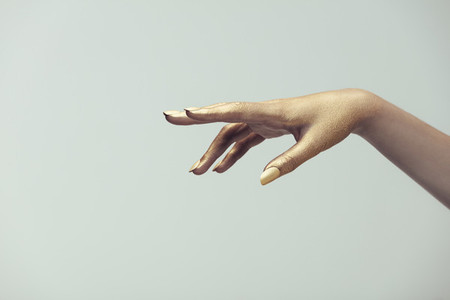 Hand of woman painted with golden color