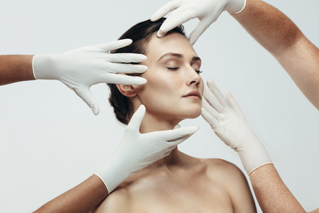 Cosmetologists examining facial skin of female