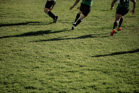 Rugby team playing match at grassy field