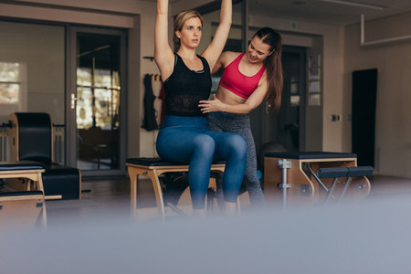 Pilates trainer instructing woman at the gym