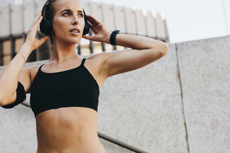 Female athlete listening to music during workout