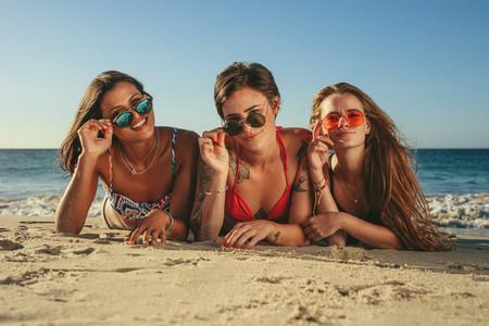 Woman friends sunbathing and enjoying at the beach