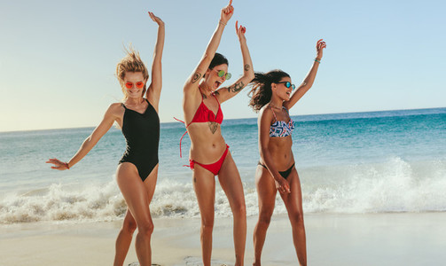 Women dancing on beach raising hands