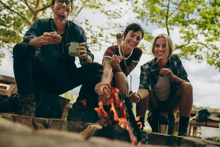 Friends camping in the countryside toasting food on bonfire