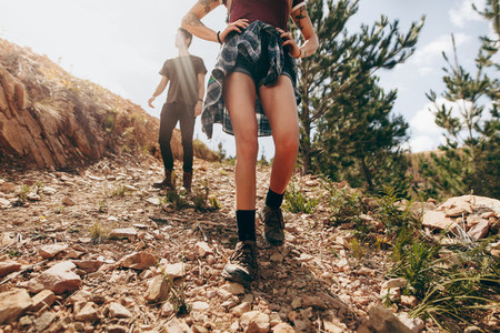 Couple on a holiday hiking down a rugged hilly terrain