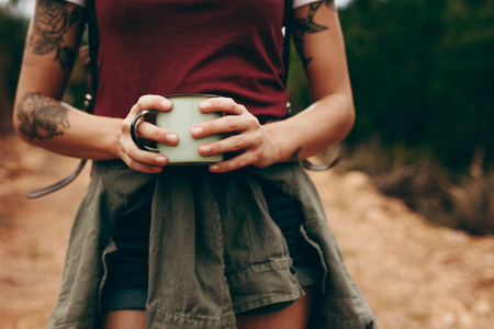 Woman holding a coffee mug while hiking in forest