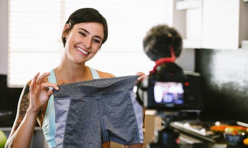 Woman making video blog on new sportswear shorts