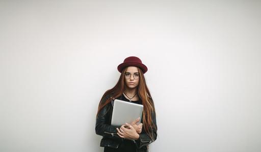Portrait of a woman entrepreneur holding a laptop