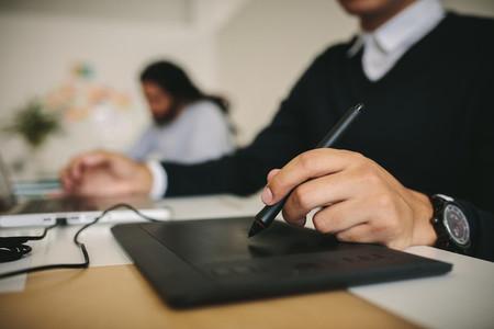 Close up of a man writing on a digital writing pad