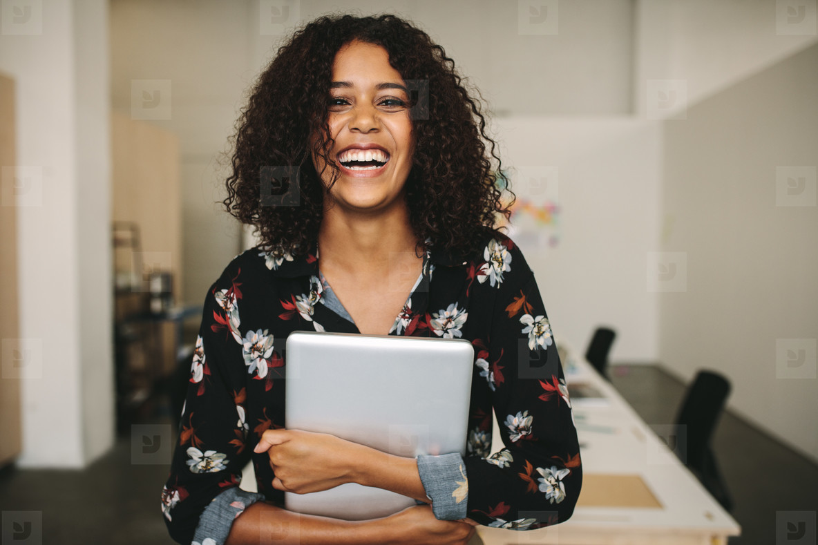 Businesswoman with a laptop in hand standing in office