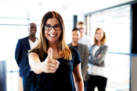 Young female executive making thumbs up sign