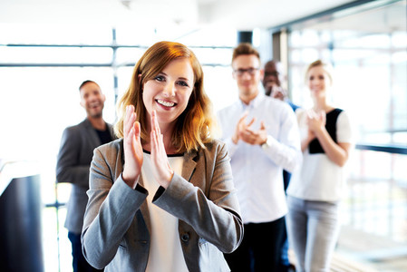 White female executive standing in front of colleagues clapping