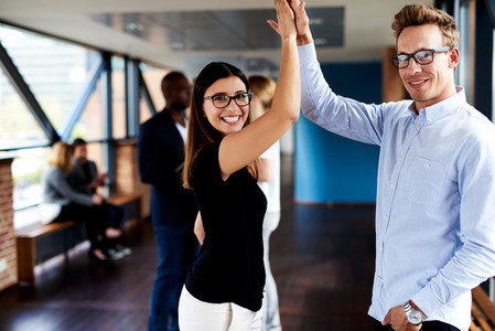 Colleagues high fiving in office hallway