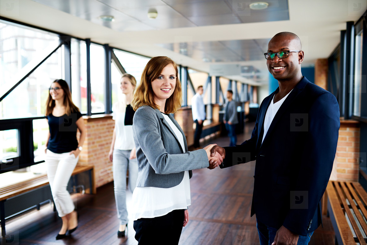 Female executive and male executive shaking hands in office hallway