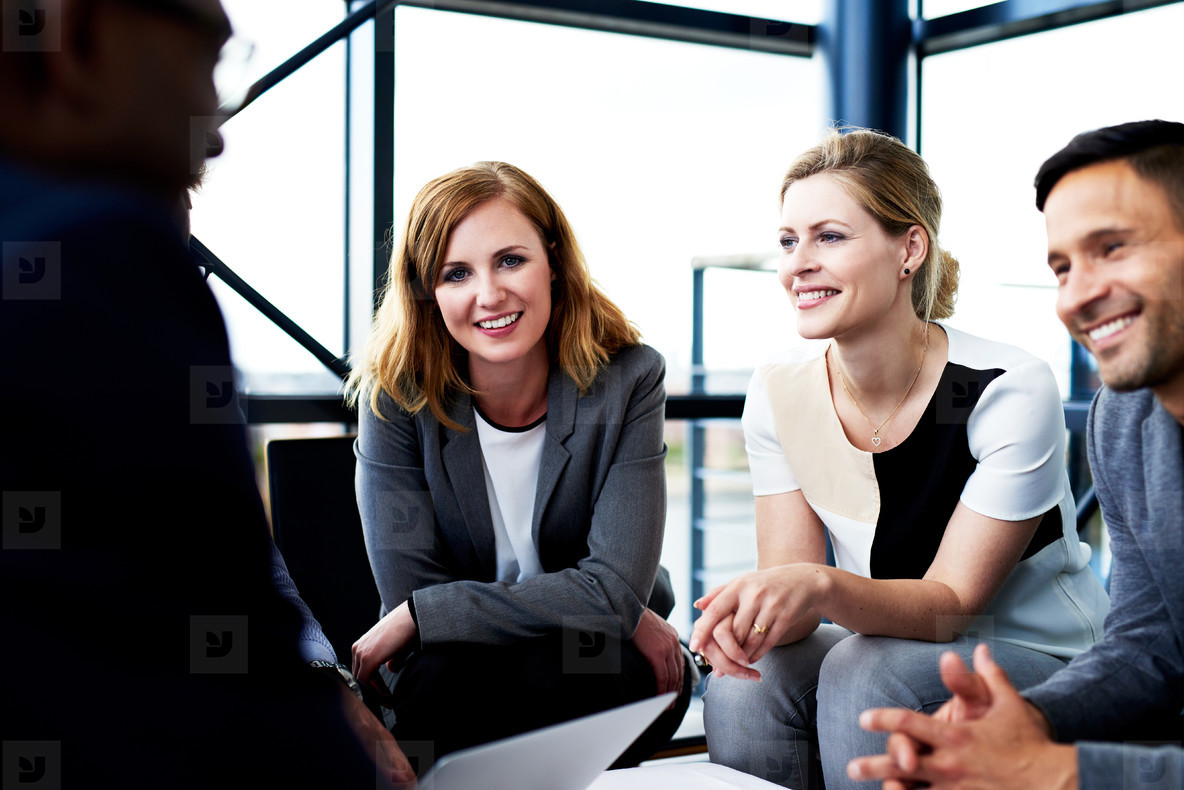 Female executive smiling at camera sitting with colleagues