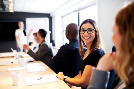 Female executive smiling at camera during work presentation