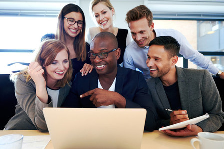 Group of executives smiling gathered around laptop