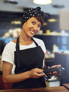 Smiling small business owner processing a sale