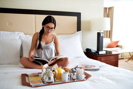Woman sitting up in bed reading book