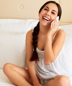 Woman wearing nightgown in bed talking on cell phone