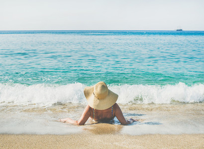 Senior woman tourist in bikini lying on sand enjoying sea